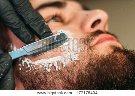 Shaving bearded man face closeup. Macro picture of barber hands with razor on male cheek. Beauty, grooming, style, modern life, fashion concept