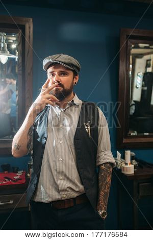 Young man smoking indoor free space. Cocky guy with tattoo standing with cigarette indoor, looking at camera. Bad habit, addiction, health, criminal concept