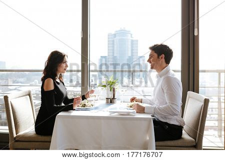 Image of young loving couple sitting in restaurant indoors while talking and eating. Looking at each other.