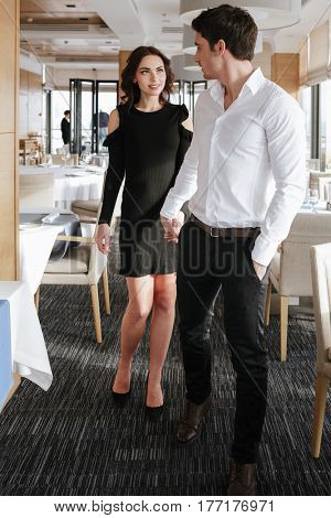 Image of young loving happy couple standing and holding hands of each other in restaurant indoors. Looking at each other.