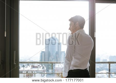 Back view image of handsome concentrated young man dressed in white shirt standing near window indoors while talking by mobile phone. Looking aside.