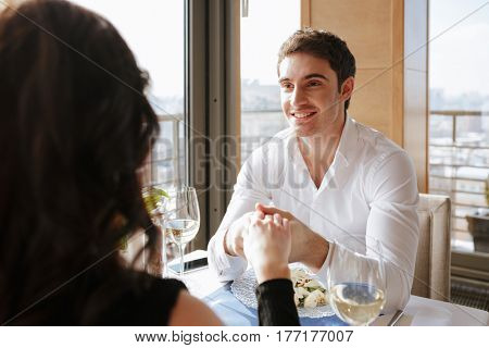 Picture of young smiling loving couple sitting in restaurant indoors while talking. Looking at each other. Focus on man.