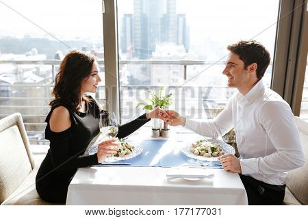 Photo of young cheerful loving couple sitting in restaurant indoors while talking and eating. Looking at each other.