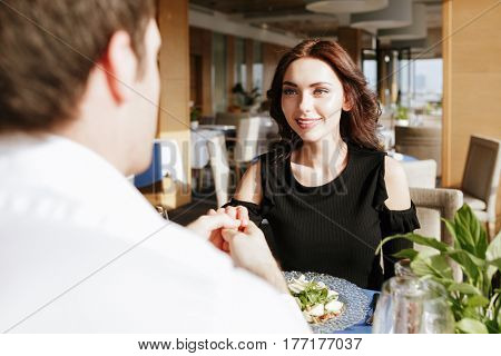 Image of young smiling loving couple sitting in restaurant indoors while talking. Looking at each other. Focus on woman.
