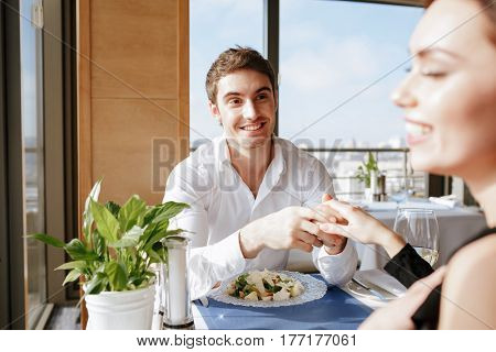 Photo of young happy loving couple sitting in restaurant indoors while talking. Looking at each other. Focus on man.