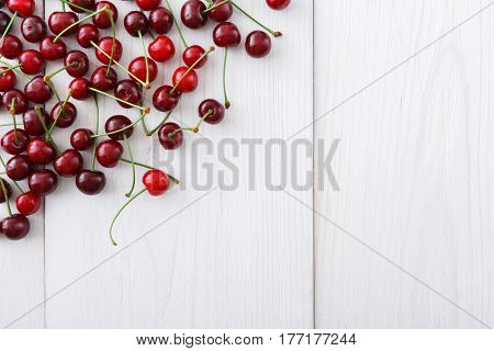 Sweet cherries on white wood background with copy space. Healthy fruits