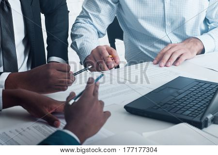 Business negotiations or meeting, preparing documents for signing. Interracial partnership.