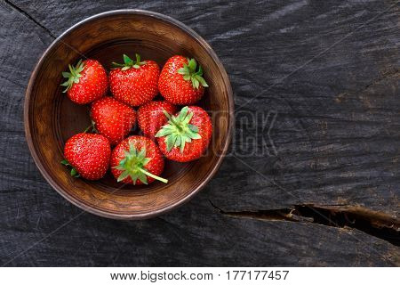 Strawberries on black rustic wood background, top view. Bowl with natural ripe organic berries with peduncles on wooden surface with copy space