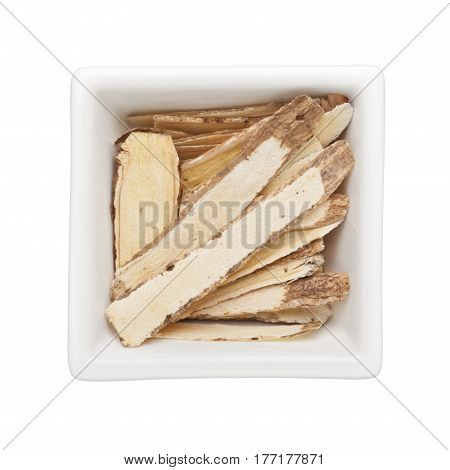 Traditional Chinese Medicine - Huang Qi (Astragalus root) in a square bowl isolated on white background