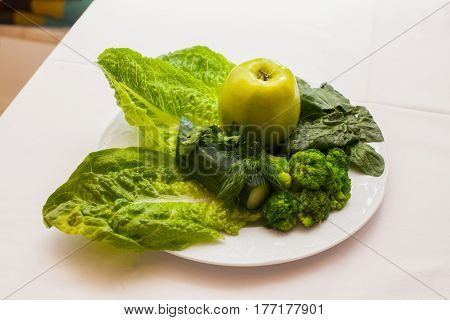 Plate of fresh mixed green salad and apple on wooden table close up