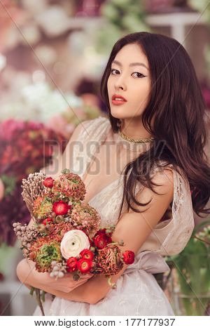 Bride. Woman in the lacy white dress with flowers peonies in hands on floral background. Asian female model posing in flower shop with bouquet of spring flowers.