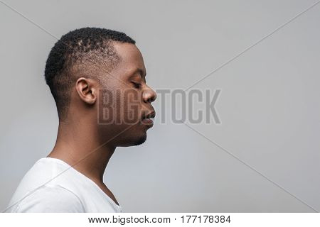 Concentrated african man with closed eyes on grey background with free space. Deep concentration, yoga, meditation. Profile view.