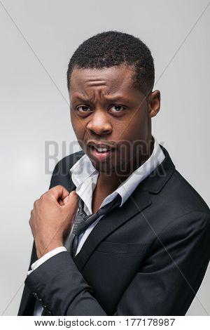 Portrait of mistrustful african american guy on grey background. Non-acceptance, antipathy, disgust.