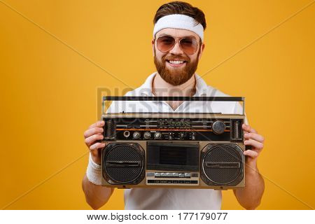 Photo of happy young man wearing sunglasses holding tape recorder dressed in white t-shirt isolated over yellow background. Looking at camera.