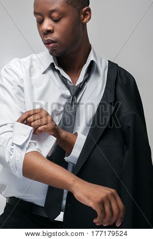 Office worker, businessman. Dress code, style, brand clothes, pricey suit. Portrait of african american man on grey background.