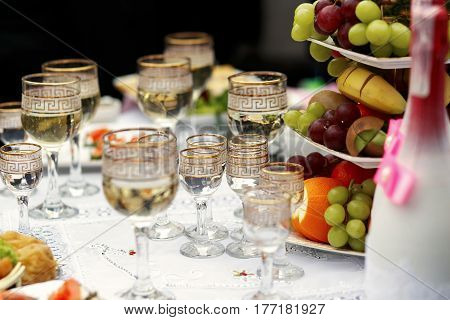 The buffet table with fruits and alcohol are near house