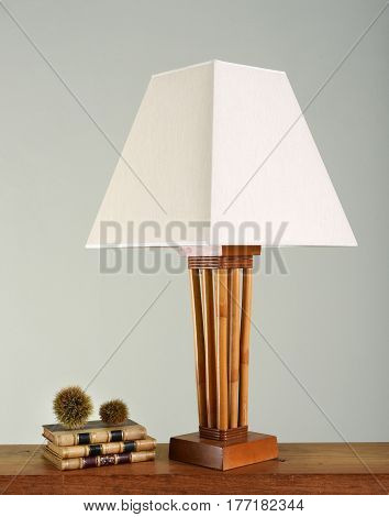 Stack Of Books Next To Vintage Lamp
