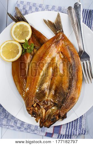 warm smoked kipper with lemon and parsley on a white plate