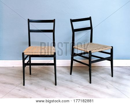 Two Simple Black Chairs With Wicker Seats