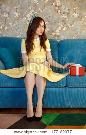 Vertical image of smiling woman in dress which sitting on sofa with gift and looking at camera