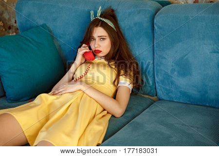 Photo of young pin-up sad lady with red lipstick lies on sofa at home. Looking at camera while talking by retro stationary phone.