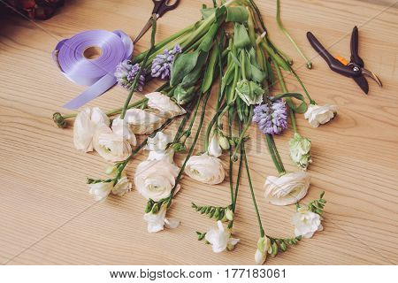 Beautiful flowers and florist equipment on wooden table