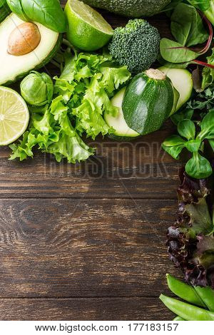 Background with assorted green vegetables, salad, avocado, cucumber, lime and Brussels sprouts on wooden table top. Healthy food concept with copy space.