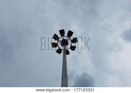 Mast With Spotlights On Stadium And Dark Sky Background.