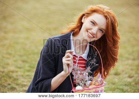 Happy pretty red head girl holding picnic basket with easter eggs outdoors