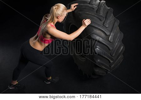 high angle view of sporty woman exercising with tire on black