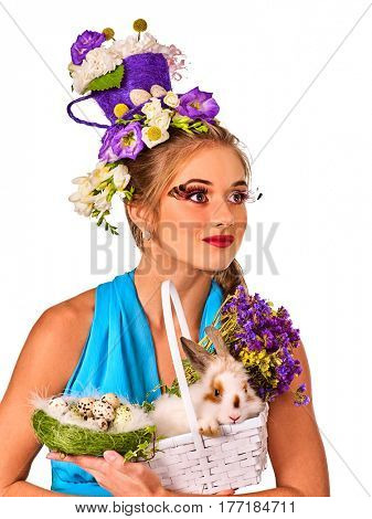 Easter dresses for women. Girl holding bunny . Woman in blue with holiday hairstyle and make up holding white rabbit in basket with flowers. Girl looking into distance. Breeding domestic animals.