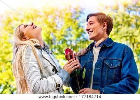 Spring couple walking park. Summer friends walk sun shine. First date of two young people in good weather day. Guy gives girl red rose flower. Girl laughs gaily with her head thrown back.