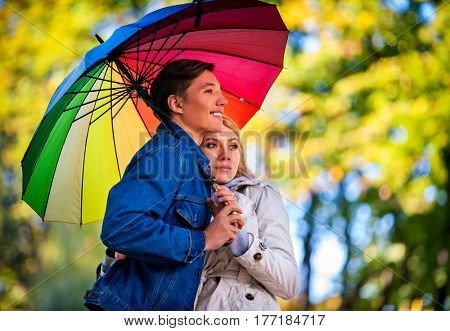 Autumn couple walking park. Fall friends walk under rain umbrella. First date of two young people in rainy day. Man laughs cheerfully.