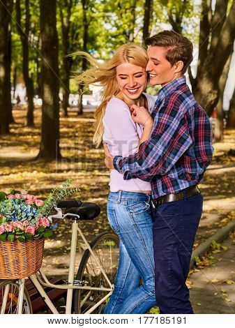 Walking bike of couple in park and kissing. Summer friends walk outdoor. First date of two young people in good weather day. Youth is dressed in jeans.
