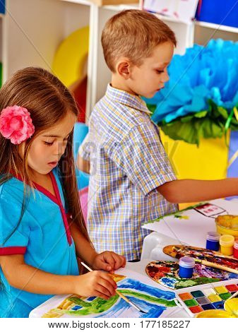 Small students girl and boy painting in art school class. Child drawing by watercolor paints on table in kindergarten. Craft drawing education develops creative abilities of children. .