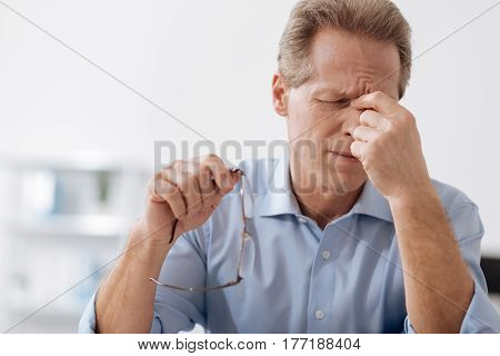 Feeling hopeless. Elderly man holding glasses in right hand while wrinkling his forehead and keeping his eyes closed