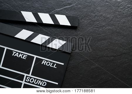 movie clapper on stone table top view