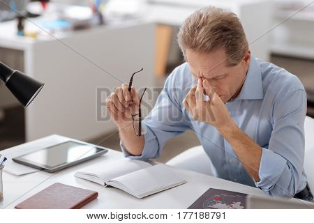 Terrible headache. Serious office worker touching his bridge of nose holding glasses in right hand while keeping his eyes closed