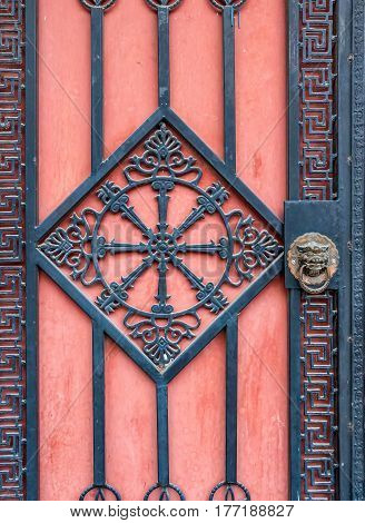 Beijing, China - Oct 30, 2016: Modern iron gate with oriental design comes with a traditional lionhead brass knocker. Image captured from a street in Old Beijing.