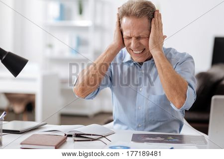 Want to have break. Office worker pressing his eyes holding hands bent in elbows while putting them on the head