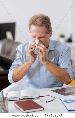 Terrible rhinitis. Disturbed office worker wearing blue shirt closing his eyes while blowing nose