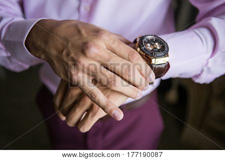 Accessories for the groom. The bride wears a wristwatch. The groom looks at his watch. Wedding detail.