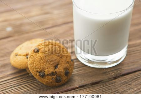 Chocolate Chip Cookies And Glass Of Milk On Wooden Table