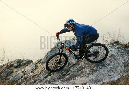 Enduro Cyclist Riding the Mountain Bike on the Rock. Extreme Sport Concept. Free Space for Text.