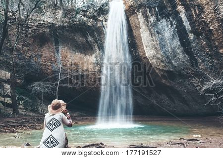 Boho woman wearing hat and poncho standing by the waterfall and looking at it. Cold weather, fall hiking. Wanderlust photo series.