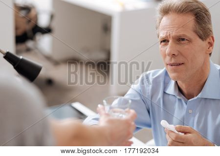 I will take. Attentive office worker holding white napkin wrinkling his forehead while taking glass
