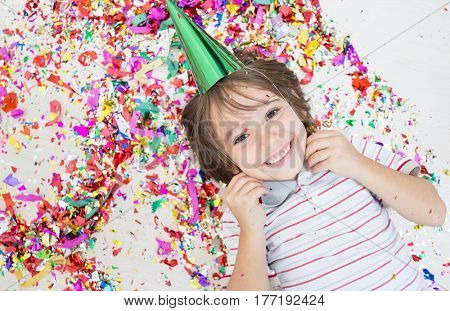Young boy blows out confetti, isolated on white background