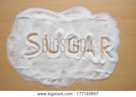 word sugar written in sugar spread out on kitchen table