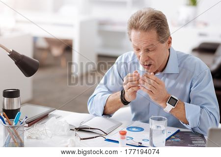 Bless you. Frustrated man wearing blue shirt, wrinkling his forehead while keeping hands opposite his mouth