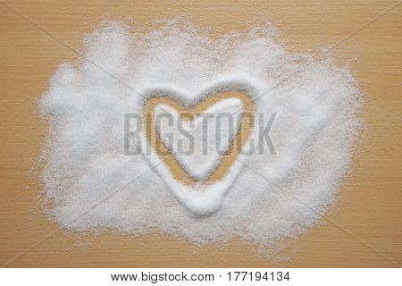 heart shape drawn in sugar spread out on kitchen table